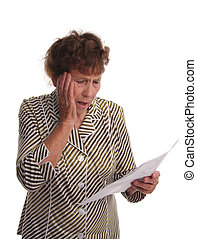 Old woman with horror looks at a sheet of paper