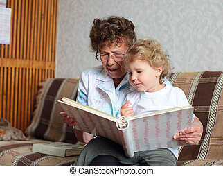 Grandmother reading book to the granddaughter