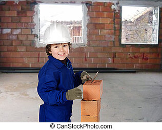 Happy little boy bricklayer building a house