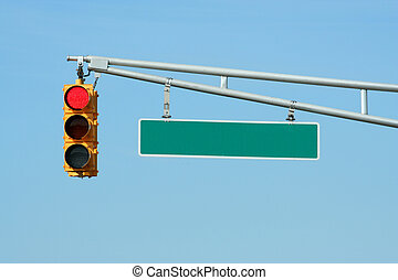 Red traffic signal light with sign on blue sky