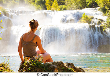 Waterfall beauty - Lovely young woman sitting at a waterfall...