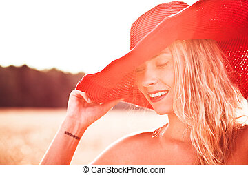 Closeup of a smiling young woman posing with a hat