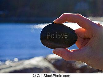 rock with believe written on it.