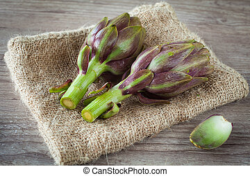 artichokes - Assortment of fresh artichokes on wooden...