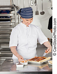 Female Chef Applying Chocolate Cream On Dough - Happy female...