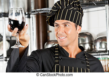 Chef Looking At Glass Of Red Wine