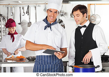 Chef With Waiter Using Digital Tablet - Portrait of male...