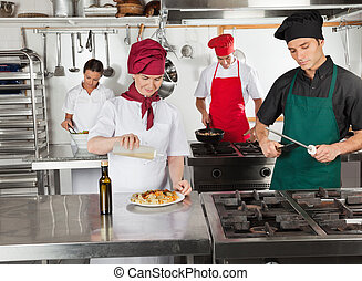 Chefs Working In Restaurant Kitchen - Female chef pouring...