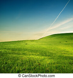 trace of airplane over green hills
