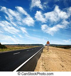long asphalt road and blue sky - long asphalt road with sand...