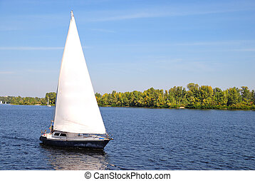sailboat on water and green island