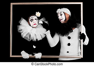two clowns in a frame, one looks sorrowful - couple of...