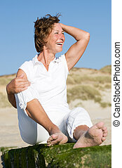 Senior woman at the beach - Senior woman sitting on a stone...