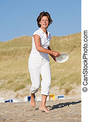 Active at the beach - Active senior woman is tossing a...