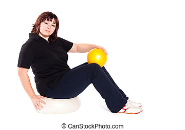 Shot of a overweight young woman exercise on fitness ball...