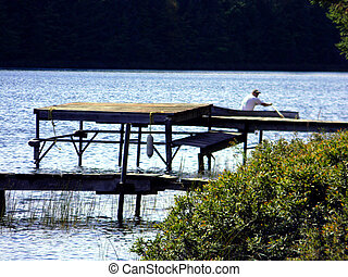 Man rowing a boat on an inland lake - photo of a man rowing...