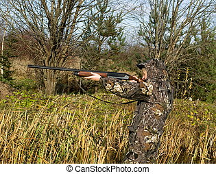 The hunter - The girl in a camouflage aiming from a gun