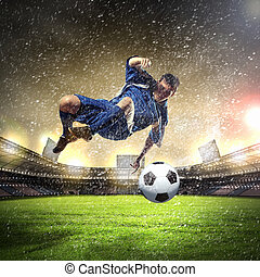 football player striking the ball - football player in blue...