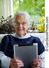Happy Elderly woman using a tablet looking at the camera and...
