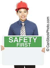 Safety First Sign - A man wearing a hardhat and holding a...