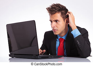 confused man looks at laptop - young business man sitting at...