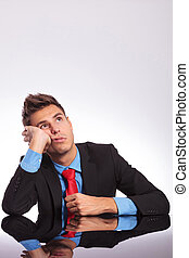 business man at desk dreaming - young business man sitting...
