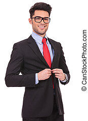 business man buttoning suit - picture of a young business...