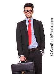 man holds suitcase and hand in pocket - young business man...
