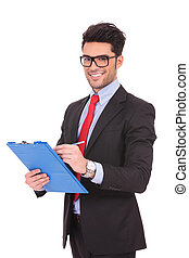 business man writes on clipboard - young business man...