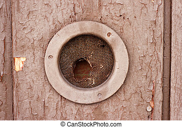 round hole in the wooden wall, closed bars