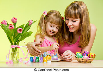 mother and daughter child painting easter eggs