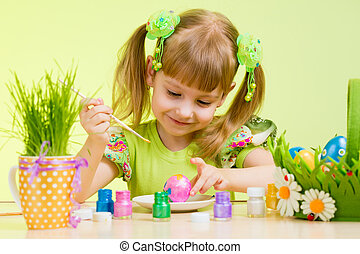 cute smiling child girl painting Easter eggs on green...