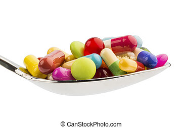 many tablets on spoon - lots of colored tablets on a spoon....