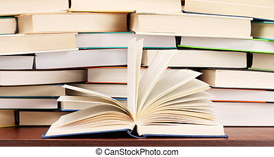 Stack of books and opened book on the table