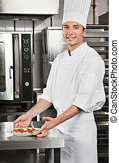 Male Chef With Pasta Dish By Counter