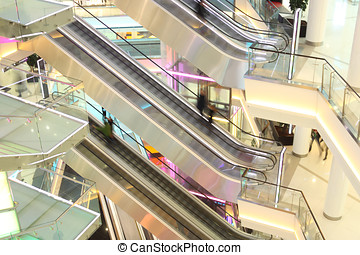 mall with escalators and people in motion