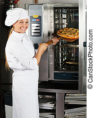 Female Chef Placing Pizza In Oven - Portrait of mid adult...