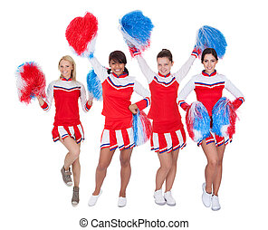 Group of young cheerleaders in red uniform. Isolated on...