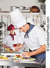 Male Chef Garnishing Dish - Young male chef garnishing dish...