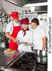 Chefs Looking For Recipe On Digital Tablet - Three chefs...