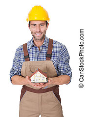 Construction worker presenting house model. Isolated on...