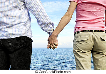Couple holding hands - Mature romantic couple holding hands...