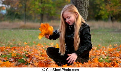 Child playing in the autumn leaves