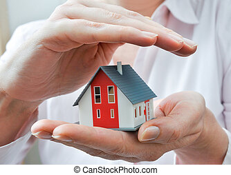 House in human hands - Hands presenting a small model of a...