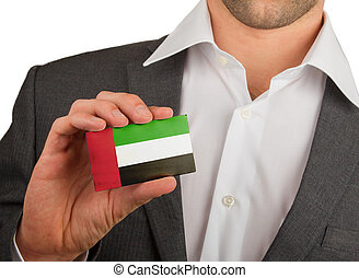 Businessman is holding a business card, UAE - Businessman is...
