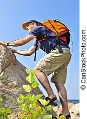Man climbing - Middle aged man with backpack climbing a rock
