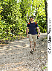 Man walking on forest trail - Happy middle aged man walking...