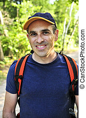 Man hiking on forest trail - Portrait of happy middle aged...