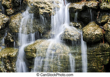 Waterfall over stones - Waterfall over natural stones in...