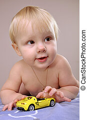 toddler boy playing with a toy car - close-up portarit of a...